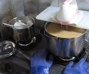 手前の大鍋がかき混ぜ中。奥のが苛性ソーダを溶かす小鍋。下の青いのはゴム手袋。